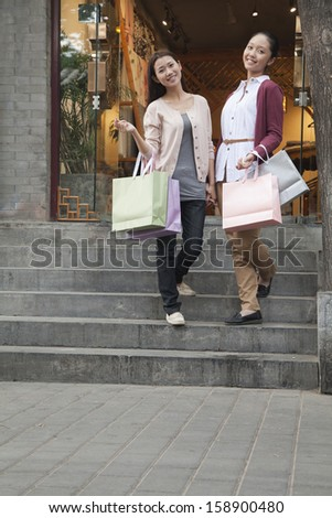 Two young women shopping looking at camera