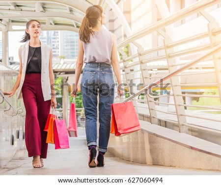 two young women shopping, sale, consumerism and people concept.