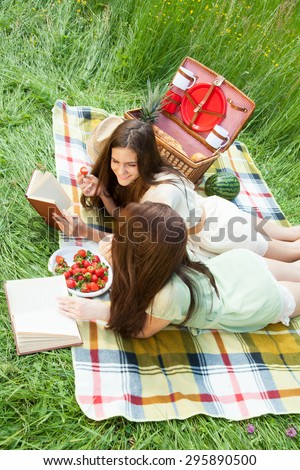 Two young women - sisters having a picnic, reading novels and eating strawberries.  - stock photo