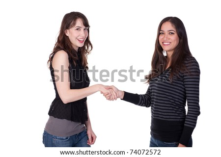 Two young women, standing and dressed casually, shaking hands and smiling