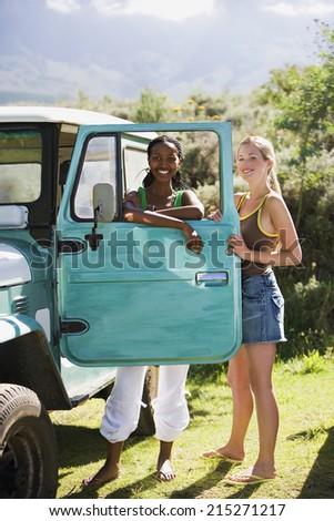 Two young women standing beside parked jeep, leaning on turquoise door, smiling, portrait