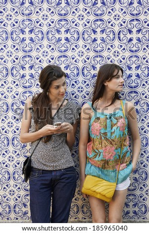 Two young women standing by patterned wall - stock photo