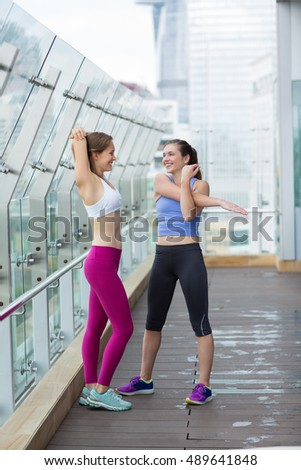 Two Young Women Stretching Hands in Fitness Club