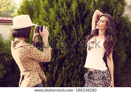 two young women take photo of each other with camera outdoor shot - stock photo
