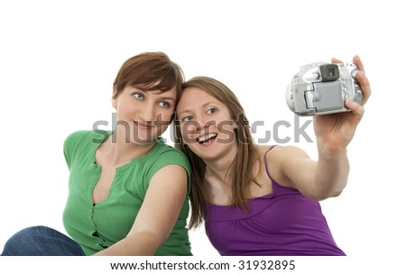 Two young women taking a self-portrait with a digital camera. - stock photo