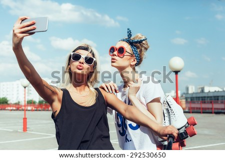 two young women taking selfie with mobile phone. Swag teen girls. Outdoor lifestyle portrait - stock photo