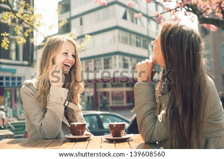 Two young women talk and drink coffee in cafe, outdoors - stock photo