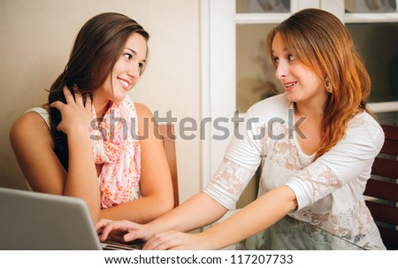 Two young women talking and laughing in front of a personal computer.