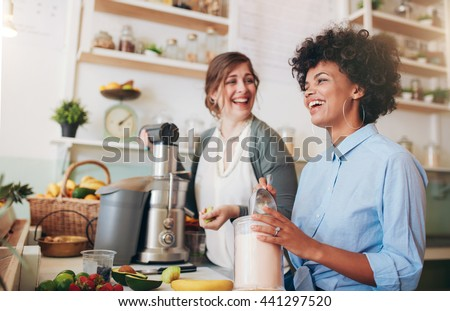 Two young women talking and smiling while working at bar counter. They are preparing fruit juice. - stock photo