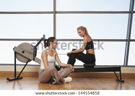 Two young women talking at rowing machine in health club