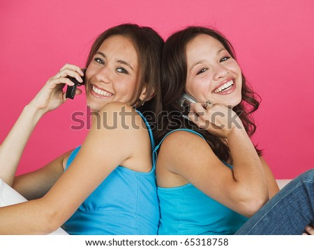 Two young women talking on cell phones