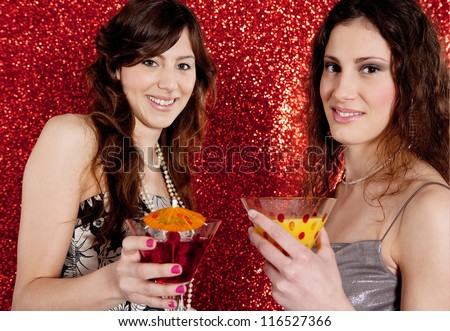 Two young women toasting and drinking cocktails while celebrating in front of a red glitter background.