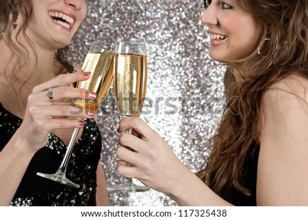 Two young women toasting with champagne at a party, against a silver glitter background. - stock photo