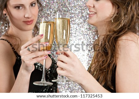 Two young women toasting with champagne at a party, against a silver glitter background.