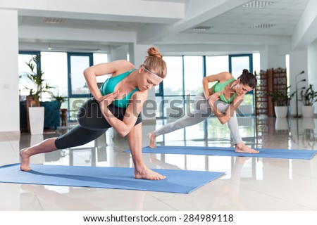 Two young women training in yoga exercise in the gym - stock photo