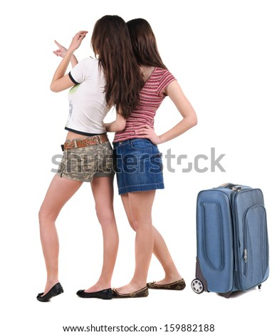 Two young women traveling with suitcas rear view. Isolated over white. - stock photo