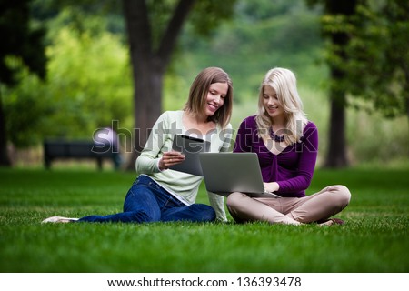 Two young women using tablet computer and laptop together