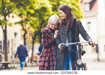 Two young women walking in Berlin. Blonde and brunette women, one is holding a bicycle, the other woman is embracing and leaning on her shoulder. Friendship and lifestyle concepts.