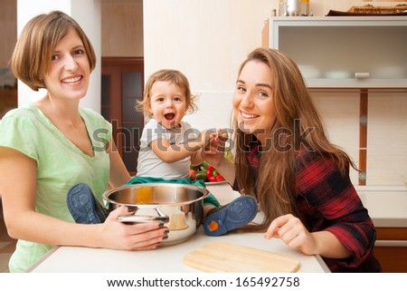 two young women with a baby in the kitchen - stock photo