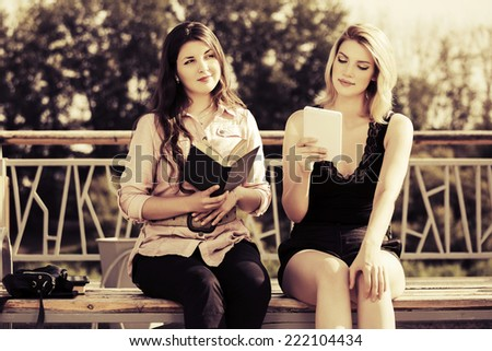 Two young women with a book and digital tablet computer - stock photo