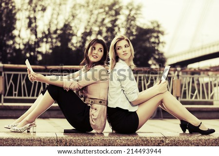 Two young women with a digital tablet computers - stock photo