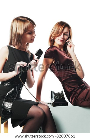 Two young women with a retro and modern phones - stock photo