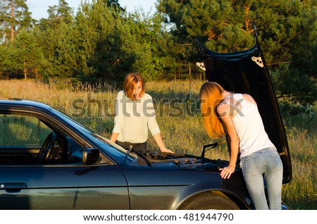 Two young women with broken down car