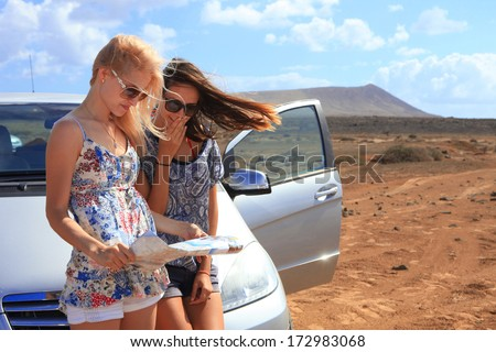 Two young women with car look at road map with mountain landscape in background - stock photo