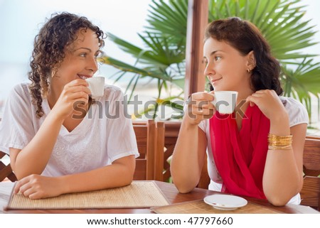 two young women with cups in hands sitting  in an arbour on seacoast, Looking against each other