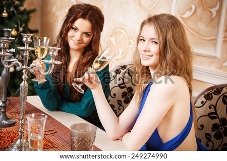 Two young women with glasses of champagne celebrating New Year - stock photo