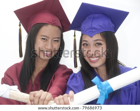 Two young women with graduation cap and gown - stock photo