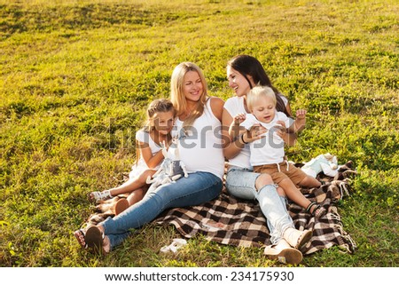 Two young women with kids enjoying sunshine in park. Beautiful pregnant woman with her friend and their kids. Mother's day concept.  - stock photo