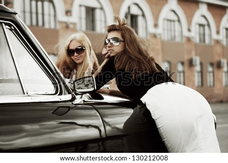 Two young women with retro car on a city street - stock photo
