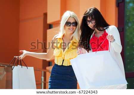 Two young women with shopping bags. - stock photo