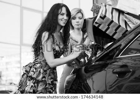 Two young women with shopping bags at the car - stock photo