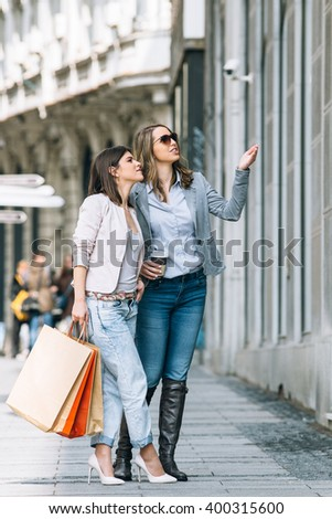 Two young women with shopping bags looking at shop window  - stock photo