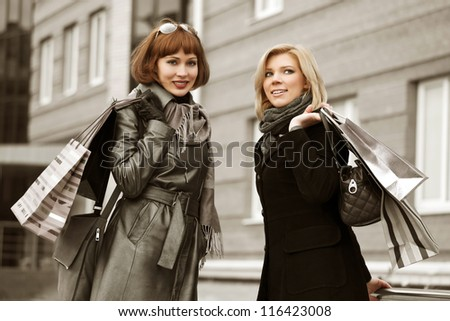Two young women with shopping bags on a city street
