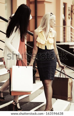 Two young women with shopping bags on the mall steps - stock photo