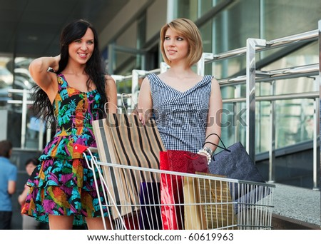 Two young women with shopping cart. - stock photo