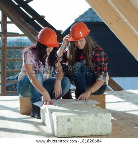 Two young women workers sitting on under construction roof, and control building in accordance with drawing