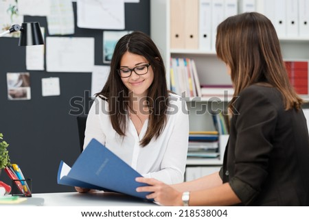 Two young work colleagues discussing some paperwork as they sit together at a desk in the office with focus to a smiling young woman in glasses - stock photo