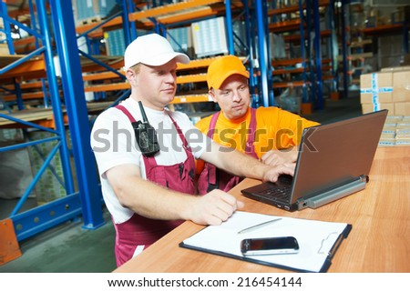 two young workers man in uniform in front of warehouse rack arrangement stillages using notebook computer