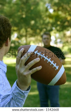 Two younger men playing a game of football, as one holds football in his hand about to throw it to the other man - stock photo