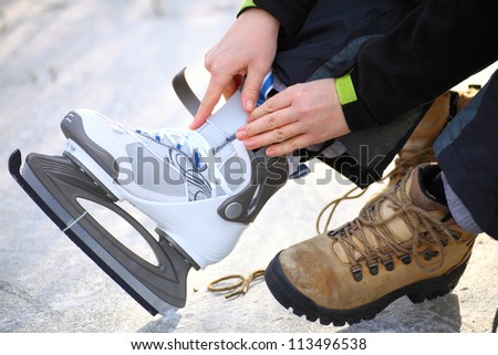 Tying laces of ice hockey skates at skating rink - stock photo