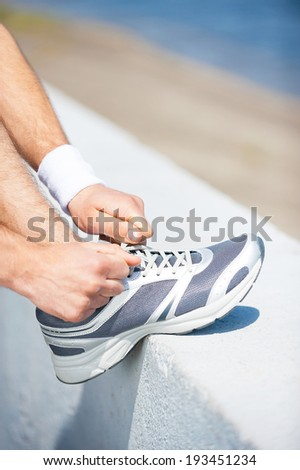 Tying shoelaces. Close-up of man tying shoelaces on sports shoe while standing outdoors  - stock photo