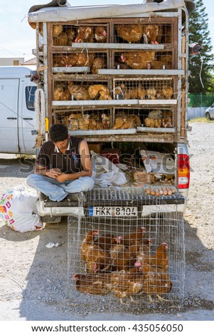TYMBAKI, CRETE, GREECE - APRIL 22. Man sells chicken, hens and chicks, in front of his car. Hen houses until the roof of the vehicle on April 22, 2016. The street market is traditional at the weekend - stock photo