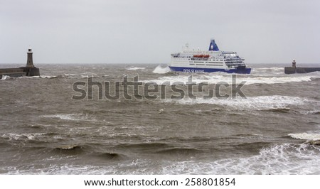 TYNEMOUTH. ENGLAND. MARCH 23, 2013. North Sea passenger ferry leaves mouth of River Tyne in very rough choppy sea. March 23, 2013, Tynemouth, England, UK. - stock photo