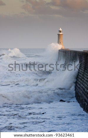 Tynemouth north pier with waves / Waves crashing against Tynemouths pier and lighthouse - stock photo