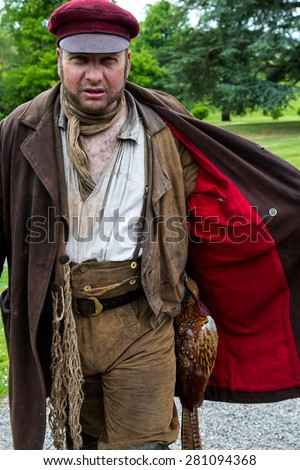 Tyntesfield, UK. 24th May 2015. Re-enactment actor pretending to be a poacher with a pheasant under his jacket - stock photo