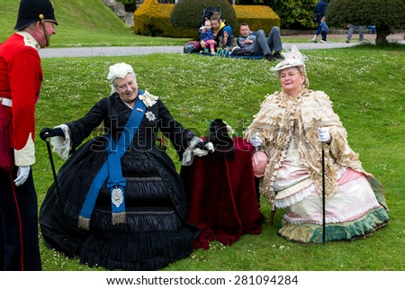 """Tyntesfield, UK. 24th May 2015. The leader from a re-enactment troupe discuss with """"Queen Victoria"""" whilst a family look on - stock photo"""